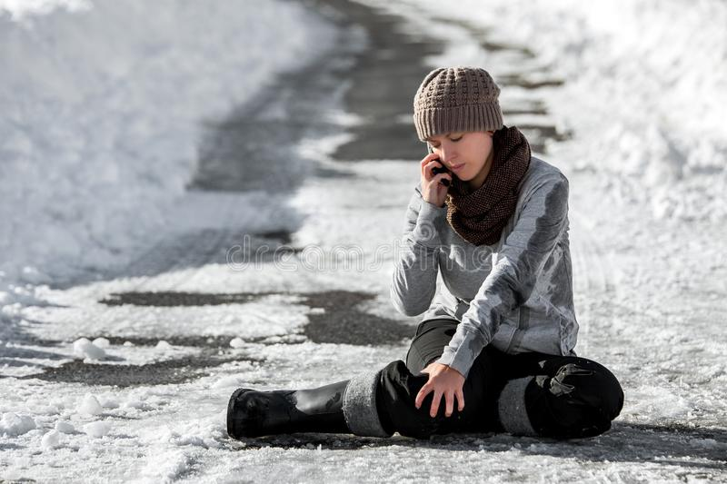 Woman slipped on winter road with black ice, emergency call for help, accident and injury royalty free stock photos