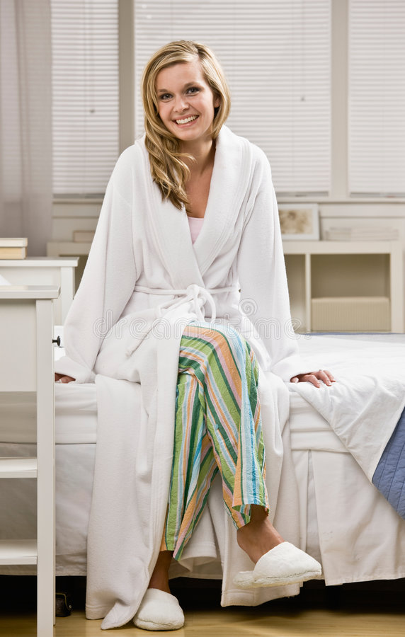 Woman in slippers and robe sitting on bed stock images
