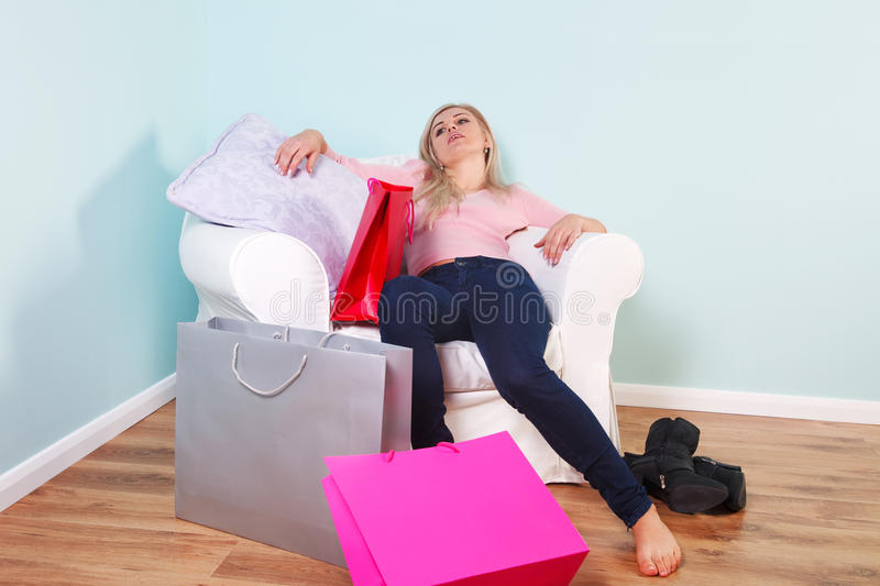 Woman slumped in an armchair after shopping trip royalty free stock photos