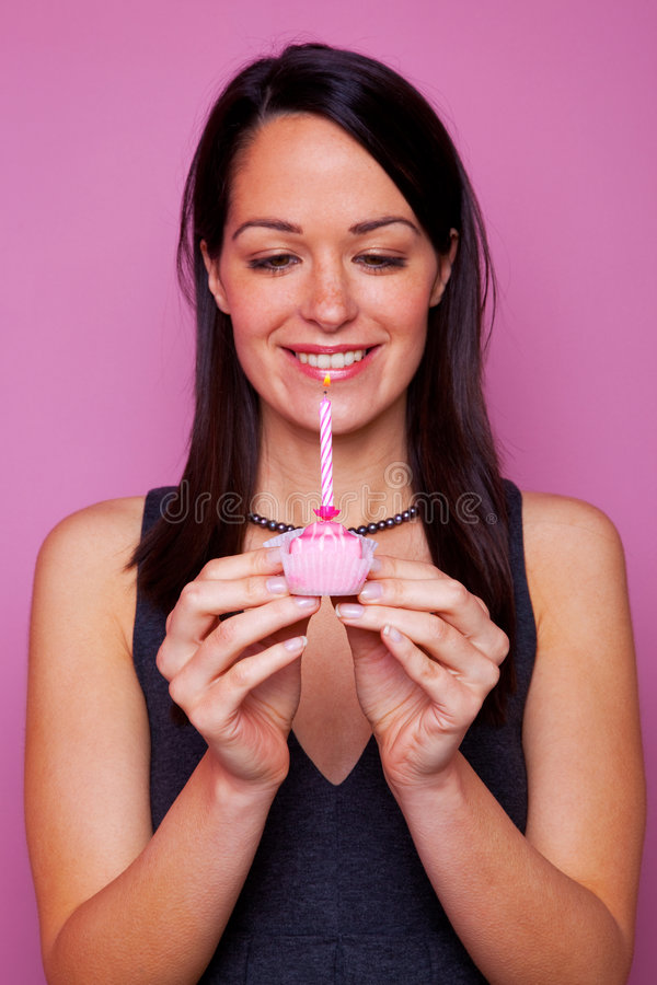 Woman with a small birthday cake. Happy brunette woman holding a small birthday cake with candle on pink background stock photo