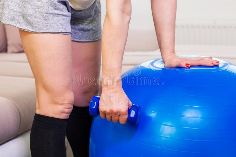 Woman with small dumbbell near fitness ball. In room royalty free stock photography