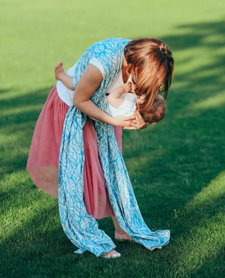 Woman small infant plays outside park meadow stock photo