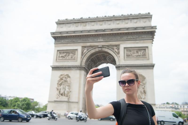Woman with smartphone at arch monument in paris, france. Woman make selfie with phone at arc de triomphe. Vacation and sightseeing. In french capital. Girl with stock photos