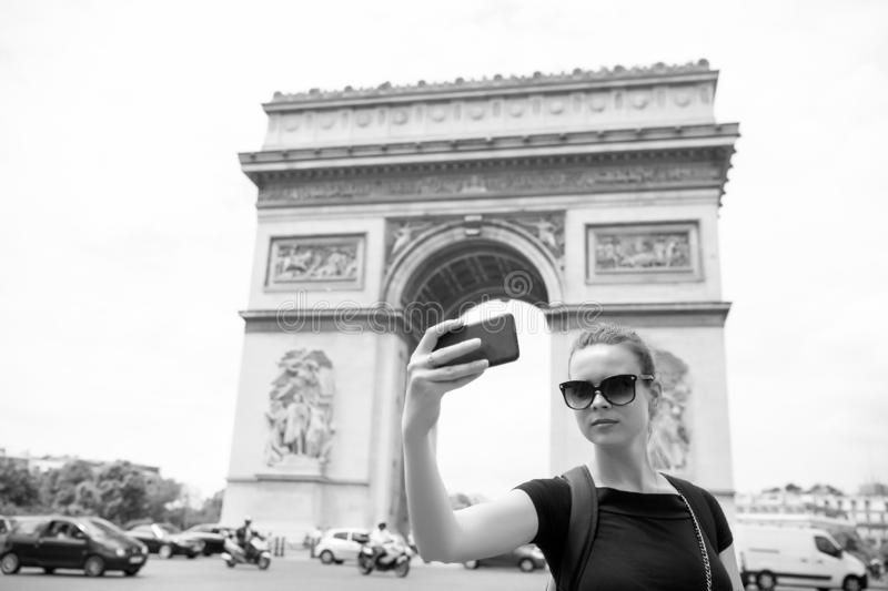 Woman with smartphone at arch monument in paris, france. Woman make selfie with phone at arc de triomphe. Vacation and. Sightseeing in french capital. Girl with royalty free stock images