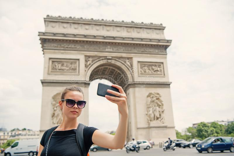 Woman with smartphone at arch monument in paris, france. Woman make selfie with phone at arc de triomphe. Vacation and stock photography