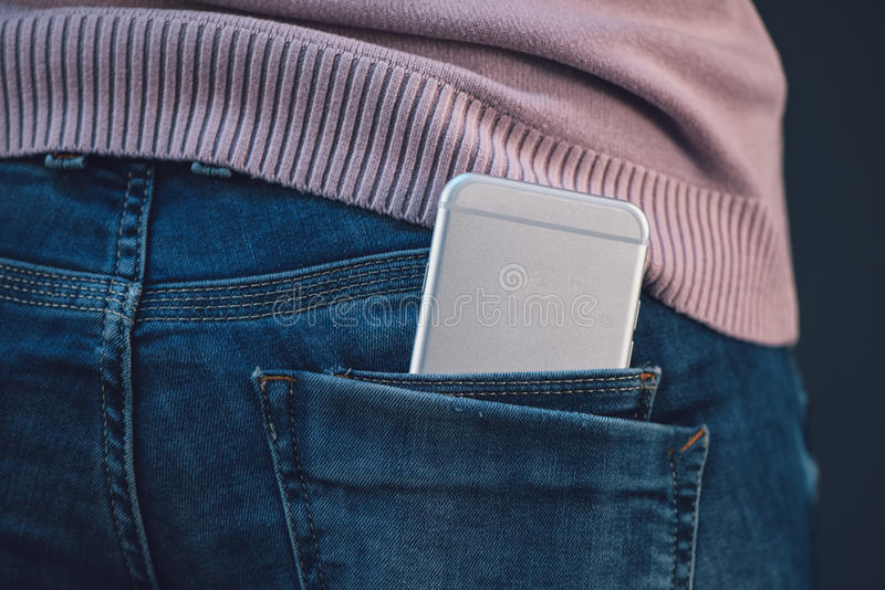 Woman with smartphone in blue jeans back pocket. Woman with new smartphone in her blue jeans trousers back pocket stock image