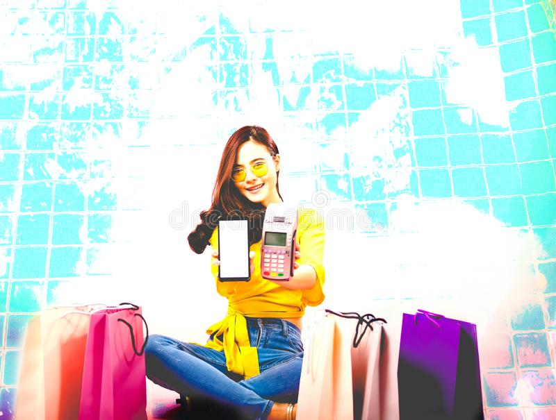 Woman with smartphone & credit card swiping machine. shopping lifestyle & payment with nfc technology. Woman with smartphone & credit card swiping machine stock photo