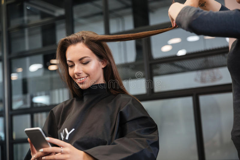 Woman with smartphone and hairdresser making hair styling at salon stock photos