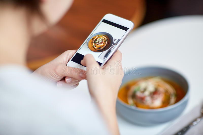 Woman with smartphone photographing food at cafe. Food, new nordic cuisine, technology, eating and people concept - woman with smartphone photographing bowl of royalty free stock photography