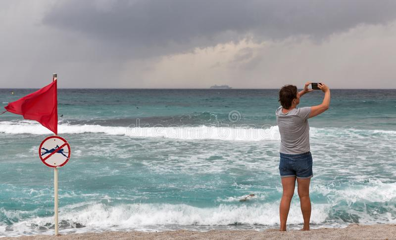 Woman with smartphone and red warning flag on sea beach stock photos