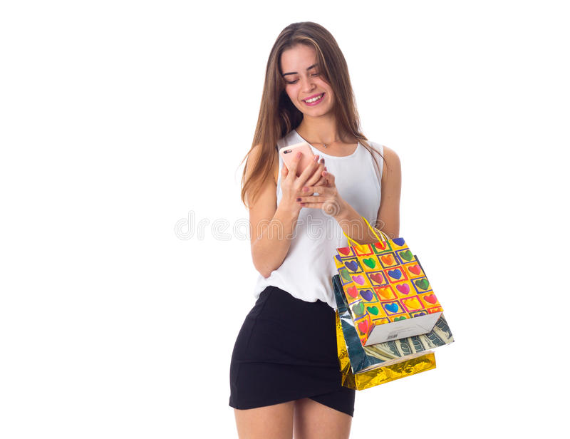 Woman with smartphone and shopping bags. Positive young woman in white blouse and black skirt with sunglasses holding shopping bags and using smartphone on white stock image