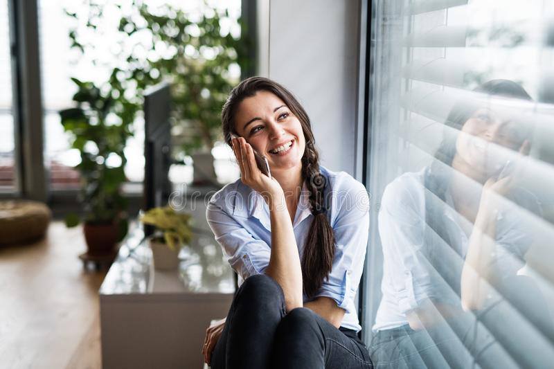 Woman with smartphone by the window at home, making a phone call. royalty free stock images