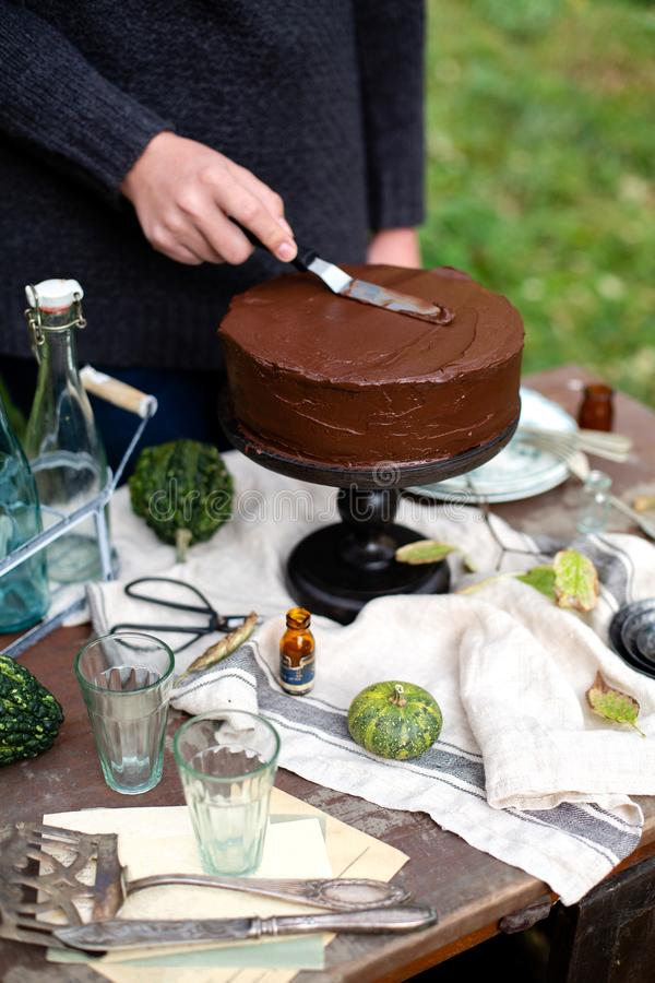 Woman smears the cake on wooden cake stand with chocolate cream. Beautiful outdoor still life in autumn garden with woman smears the cake on wooden cake stand stock images