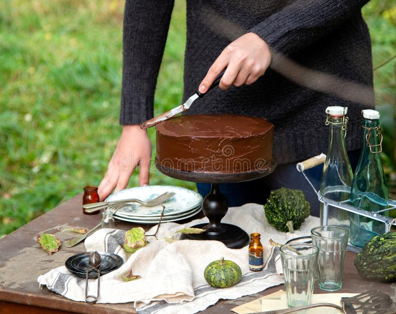 Woman smears the cake on wooden cake stand with chocolate cream. Beautiful outdoor still life in autumn garden with woman smears the cake on wooden cake stand stock photos