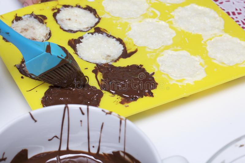 A woman smears chocolate filling coconut and condensed milk. Ingredients for dessert are on the table. Cooking sweets with coconut royalty free stock image