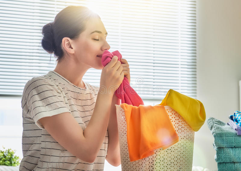 Woman is smelling clean clothes. Beautiful young woman is smelling clean clothes and smiling while doing laundry at home royalty free stock photos