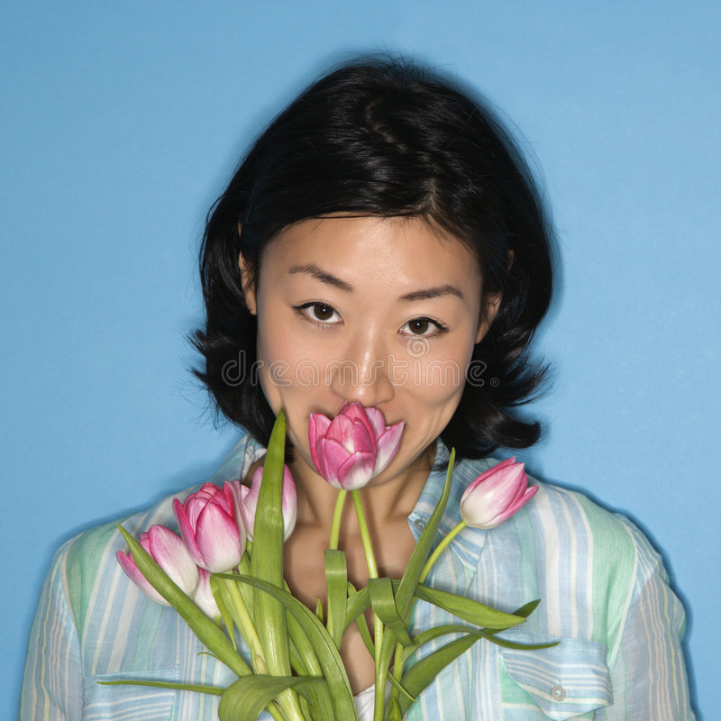 Woman smelling flowers. stock image