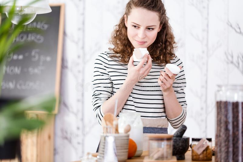 Woman smelling soaps. Woman smelling organic soaps while standing in a cosmetic shop stock image