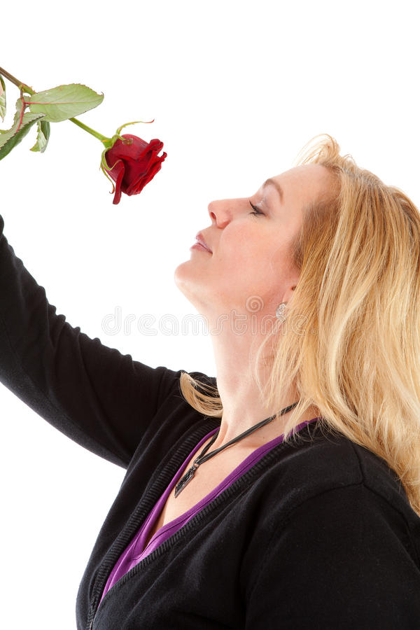 Woman smelling a red rose royalty free stock photos