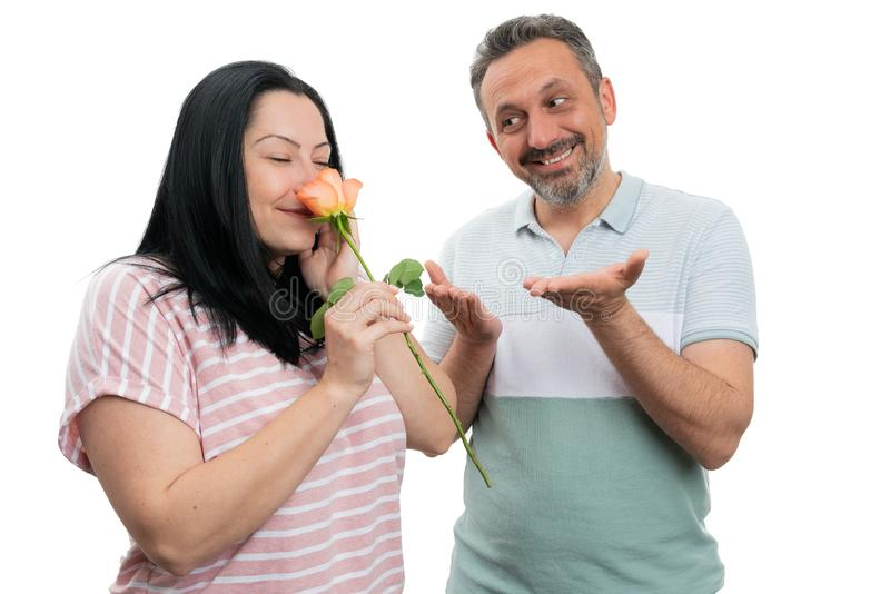 Woman smelling rose gift from man stock photo