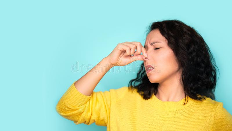 Woman smelling something stinky and disgusting, intolerable smell, holding breath with fingers on nose. Bad smells.  stock images