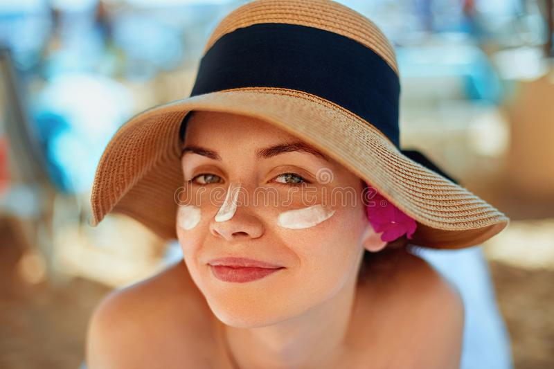 Woman smile applying sun cream on face. Skincare. Body Sun protection. sunscreen. Female in hat smear moisturizing lotion on skin stock photo