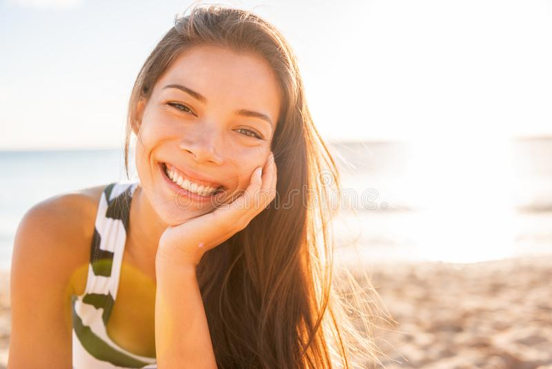 Woman smile happy on beach with healthy glowing skin on sunset sun flare rays summer background. Asian girl smiling confident stock photo