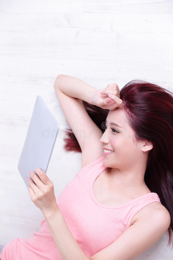 Woman smile using tablet pc. Happy young beautiful woman relax lying and using digital tablet pc, asian beauty stock images