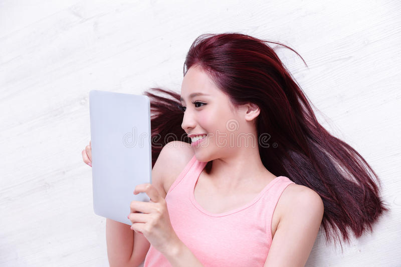 Woman smile using tablet pc. Happy young beautiful woman relax lying and using digital tablet pc, asian beauty royalty free stock photography