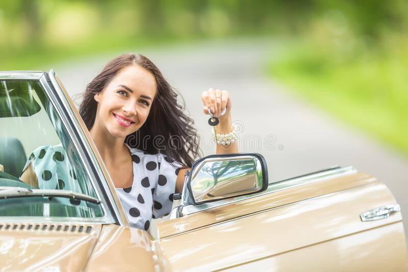 Woman smiles holding car keys in her hand sitting into a convertible vintage car stock photography