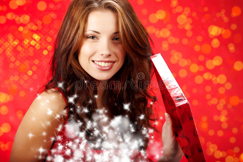 Woman smiles and holding a magic gift in packing