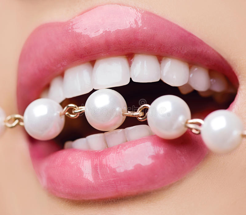 Woman smiles showing white teeth. Holding a pearly necklace into the mouth stock photo