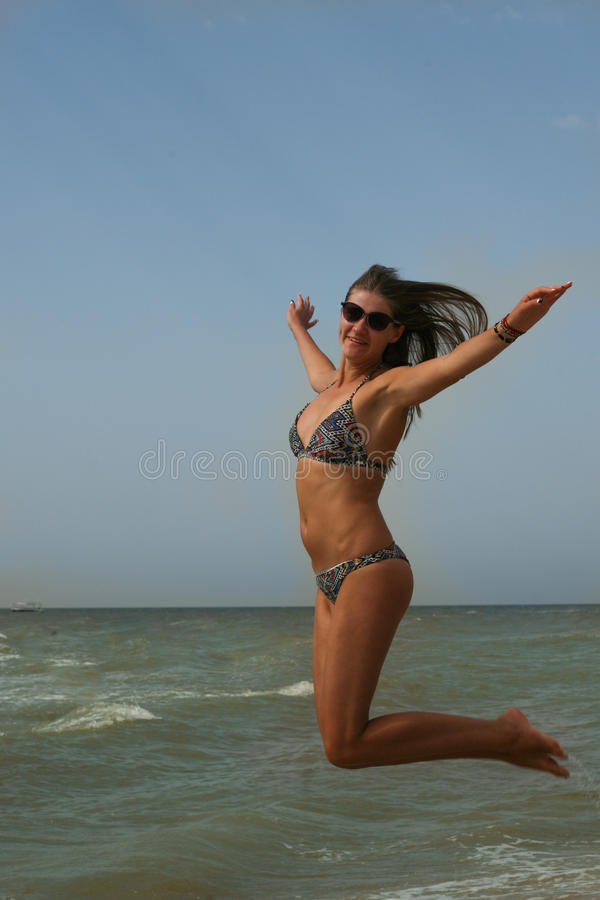 Woman smiling arms raised up to blue sky, is jumping, celebrating freedom. Positive human emotions, face expression feeling life p. Woman smiling arms raised up stock photos