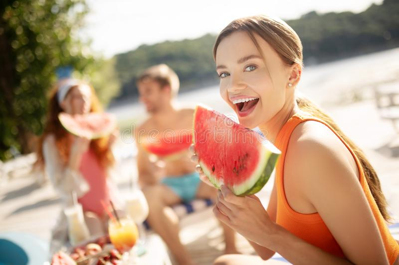 Beautiful blue-eyed woman smiling while eating watermelon stock photography