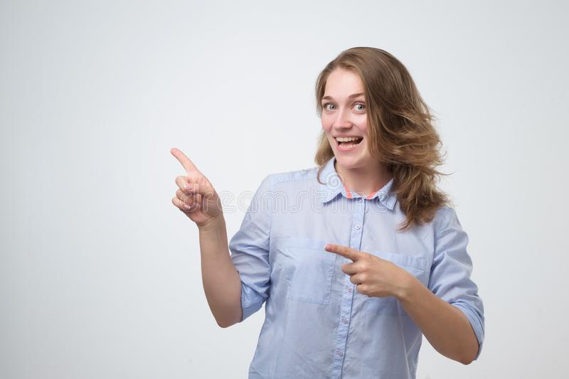 Woman smiling broadly at camera, pointing fingers away, showing something interesting royalty free stock images