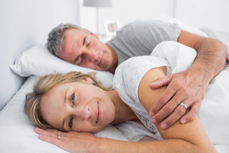 Woman smiling at camera as husband is sleeping stock image