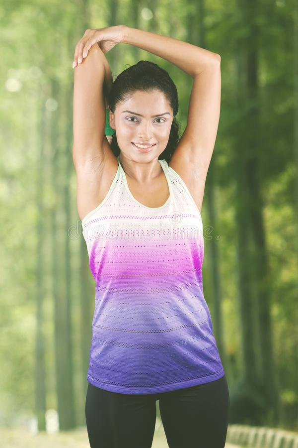 Woman smiling at camera while stretching arms stock images
