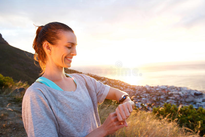 Woman smiling checking her watch for time by sunset stock photo