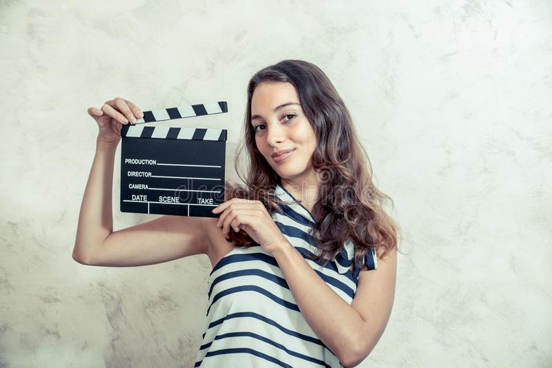 Woman smiling with clapper board movie audition concept stock photography