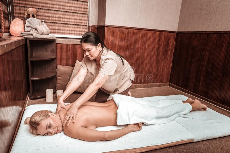 Woman smiling during her neck and back massage. Healing back muscles. Relaxed women lying near masseuse on a mat smiling during her neck and back massage stock photo