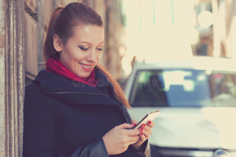 Woman smiling holding a mobile phone standing outdoors next to new car royalty free stock images