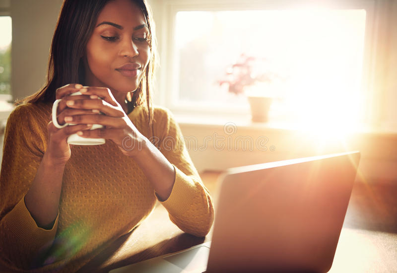 Woman smiling holding white mug. Adult woman smiling sitting near bright window while looking at open laptop computer on table and holding white mug royalty free stock image