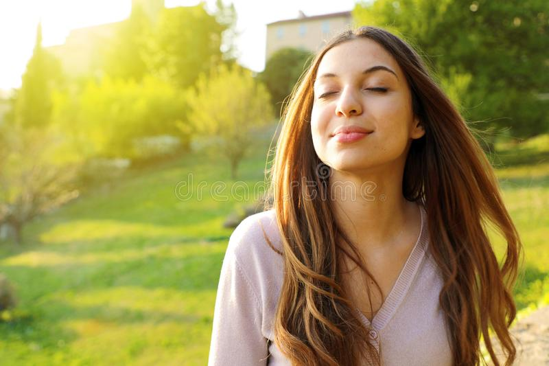Woman smiling looking up taking deep breath celebrating freedom. Positive human emotion face expression feeling life perception stock photo
