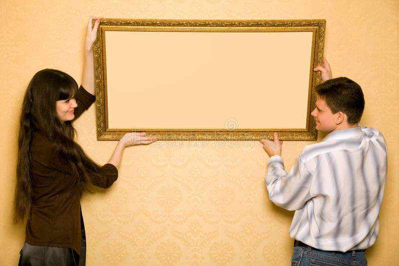 Woman and smiling man hang up on wall picture. Young beautiful woman and smiling man hang up on wall picture in frame, looking at picture royalty free stock image