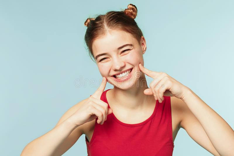 Woman smiling with perfect smile on the blue studio background stock photography