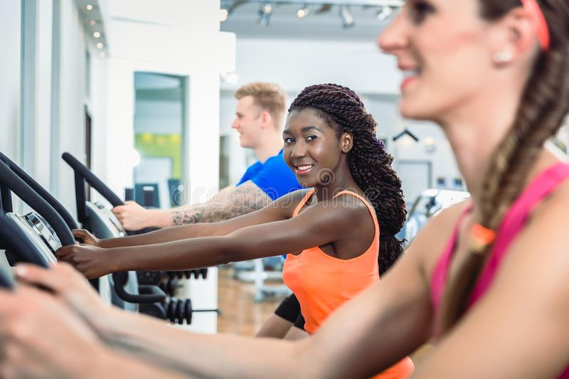 Woman smiling running on treadmill in the gym modern health club stock photos