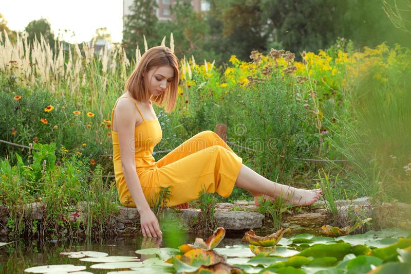 Woman smiling sitting in the garden near green bushes and a fountain. Cute Woman smiling sitting on a stone posing in the garden near green bushes and a fountain royalty free stock photo
