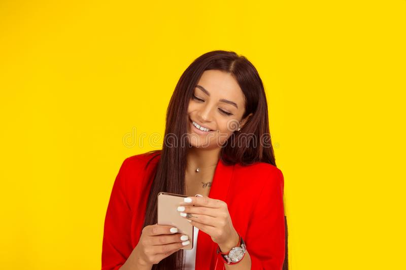 Woman smiling while texting on smartphone isolated on yellow royalty free stock photo