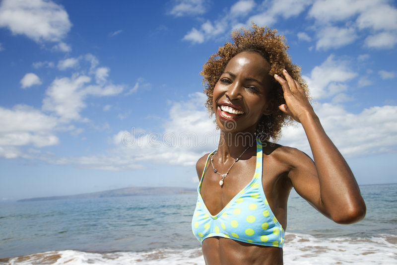 Woman smiling and touhing hair. royalty free stock photography