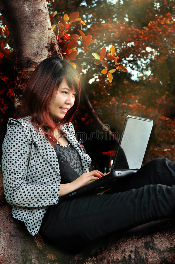 Woman smiling on the tree and playing laptop royalty free stock images